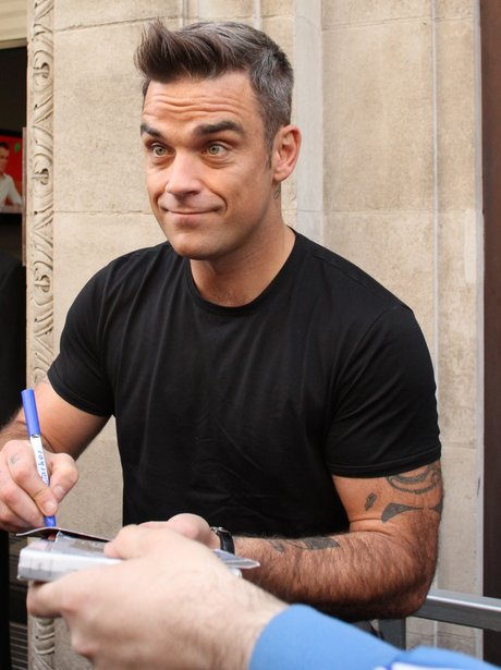 Robbie Williams signs autographs for fans