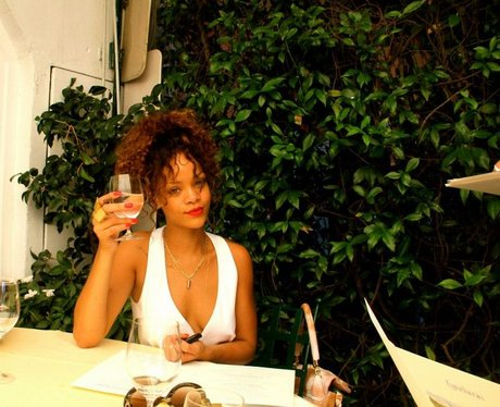 Rihanna enjoys some champagne on holiday.
