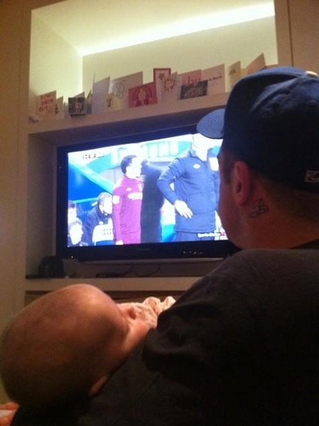 Robbie Williams watching the tv with his baby