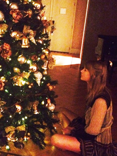 Taylor Swift sitting next to her Christmas tree
