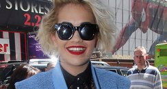 Rita Ora wears leather shorts and sunglasses